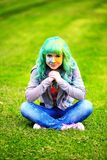 Beautiful hipster alternative young woman with green hair sits on grass Stock Photo