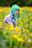 Beautiful hipster alternative young woman with green hair sits in grass with dandelion in park Stock Photography