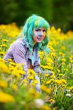 Beautiful hipster alternative young woman with green hair sits in grass with dandelion in park Royalty Free Stock Image