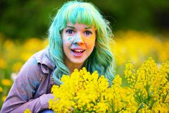 Beautiful hipster alternative young woman with green hair sits in grass with dandelion in park Royalty Free Stock Photos