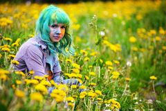Beautiful hipster alternative young woman with green hair sits in grass with dandelion in park Stock Photo