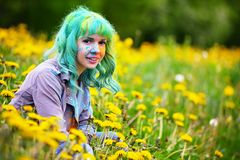 Beautiful hipster alternative young woman with green hair sits in grass with dandelion in park Stock Photos