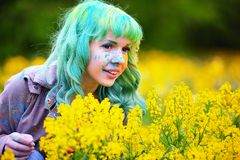 Beautiful hipster alternative young woman with green hair sits in grass with dandelion in park Stock Image