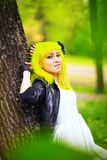 Beautiful hipster alternative young woman with yellow hair in park Stock Image