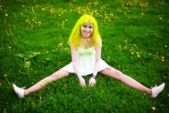 Beautiful hipster alternative young woman with yellow hair sits on grass Stock Photography