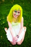 Beautiful hipster alternative young woman with yellow hair sits on grass Royalty Free Stock Photo