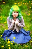 Beautiful hipster alternative young woman with yellow hair sits in grass with dandelion in park Stock Photo