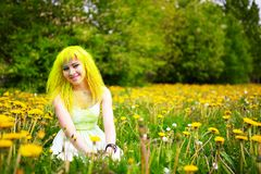 Beautiful hipster alternative young woman with yellow hair sits in grass with dandelion in park Royalty Free Stock Image