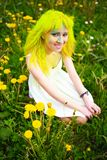 Beautiful hipster alternative young woman with yellow hair sits in grass with dandelion in park Royalty Free Stock Photography
