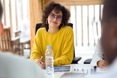 Beautiful hipster businesswoman paying attention to her partners on coworking place. Shot of beautiful hipster businesswoman paying attention to her partners on royalty free stock image