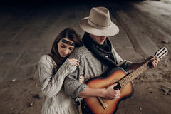 Beautiful hipster couple, handsome cowboy man guitar musician an Royalty Free Stock Images