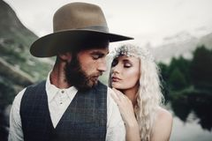 Stylish young wedding couple posing in beautiful Matterhorn moun. Beautiful hipster couple hugging on top of mountains. romantic moment of stylish family royalty free stock images