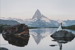 Stylish young wedding couple posing in beautiful Matterhorn moun. Beautiful hipster couple hugging on top of mountains. romantic moment of stylish family royalty free stock photography