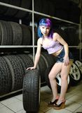Beautiful hipster girl automobile mechanic works with tires on wheels Stock Images