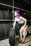 Beautiful hipster girl automobile mechanic works with tires on wheels Royalty Free Stock Images