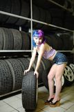 Beautiful hipster girl automobile mechanic works with tires on wheels Stock Photo