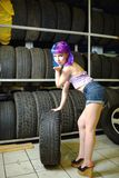 Beautiful hipster girl automobile mechanic works with tires on wheels Royalty Free Stock Photo