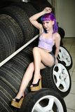 Beautiful hipster girl automobile mechanic works with tires on wheels Royalty Free Stock Photography