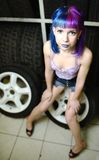Beautiful hipster girl automobile mechanic works with tires on wheels Royalty Free Stock Photos