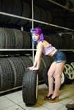 Beautiful hipster girl automobile mechanic works with tires on wheels Royalty Free Stock Image