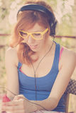Beautiful hipster girl with big headphones listening to the musi Royalty Free Stock Image