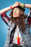 Beautiful hipster girl with black beanie hat with hands up looking down at the camera. Beautiful hipster girl with curly hair wearing red checkered shirt,denim Royalty Free Stock Photography