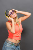 Beautiful hipster girl in earphones and sunglasses posing in photo studio Royalty Free Stock Photography