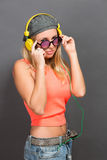 Beautiful hipster girl in earphones and sunglasses posing in photo studio Stock Images