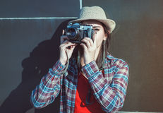 Beautiful hipster girl in hat making picture with retro camera Royalty Free Stock Image