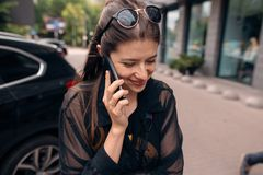 Beautiful hipster girl holding phone and talking in city street. Stylish happy woman having conversation by smartphone and smiling. space for text Stock Photo
