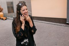 Beautiful hipster girl holding phone and talking in city street. stock photos