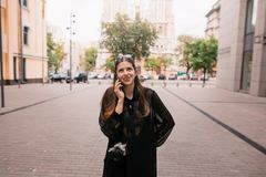 Beautiful hipster girl holding phone and talking in city street. royalty free stock photo