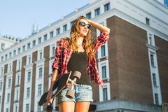 Beautiful hipster girl with skate board wearing sunglasses royalty free stock images