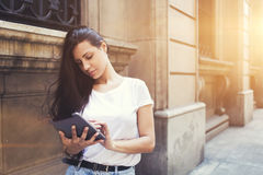 Beautiful hipster girl is using on touch pad in urban setting Stock Photos
