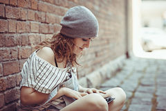 Beautiful hipster girl works on the tablet on the internet Royalty Free Stock Image