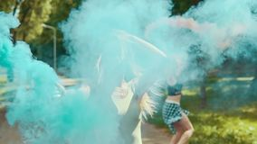 Beautiful hipster girls runs in park waving colored smoke. Young girls have fun stock video footage