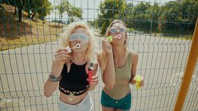 Beautiful hipster girls in sunglasses having fun making bubbles outdoors stock footage