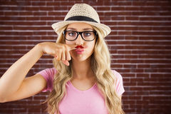 A beautiful hipster having a fake distinguished mustache Stock Photo