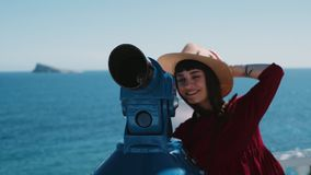 Excited brunette adventures in summer holidays. Beautiful hipster millennial woman in red dress and straw hat looks through pay per view telescope on beach stock footage