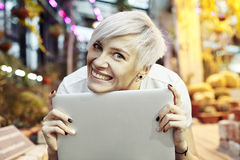 Beautiful hipster woman blonde short hair close-up portrait smiling and holding portable computer. Sunny day in a park or garden. Stock Photography