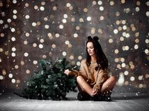 Beautiful hipster woman with Christmas fir tree and lights in knitted sweater blouse. Under snow in loft restaurant stock photo