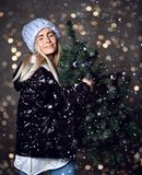 Beautiful hipster woman with Christmas fir tree and lights in sexy knitted sweater blouse royalty free stock photo
