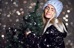 Beautiful hipster woman with Christmas fir tree and lights in sexy knitted sweater blouse royalty free stock image