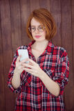 Beautiful hipster woman concentrating on her smartphone. Against a wooden background stock image