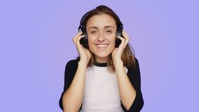 Beautiful hipster woman listens to music. Beautiful pretty cute and funny girl, teenager or young woman in millennial hipster outfit on purple background listens stock video