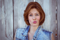 Beautiful hipster woman making a funny face. Against a wooden background Royalty Free Stock Photo