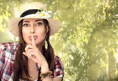 Beautiful Hipster Young Woman Hushing at Camera in the Garden Royalty Free Stock Images