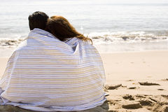 Beautiful Hispanic couple wrapped in a blanket. Royalty Free Stock Photos