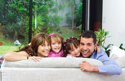 Beautiful hispanic family of four posing with. Heads sticking up from back of sofa looking at camera smiling Stock Image