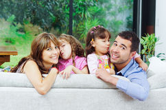 Beautiful hispanic family of four posing with. Heads sticking up from back of sofa looking at camera smiling Stock Photography
